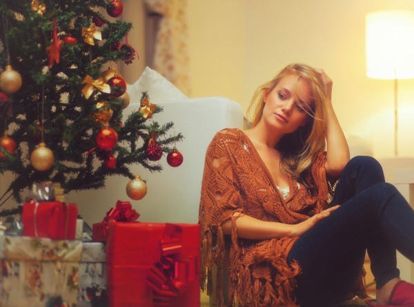 Young Woman Sitting Near A Christmas Tree
